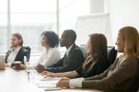 Die verschiedenen lächelnden Geschäftsleute, die am Konferenztische bei der Gruppensitzung oder bei der Unternehmensanweisung, in den afrikanischen und kaukasischen Geschäftsmännern und in den Geschäftsfraupartnern sitzen, team, an Trainingskonzept teilzunehmen Standard-Bild
