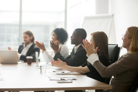 Gemischtrassige Geschäftsleute, die das Sitzen am Konferenztische, klatschende Hände des verschiedenen Teams nach Gruppensitzung, multinationales dankbares Publikum zujubeln applaudieren, Darstellung oder Training schätzend