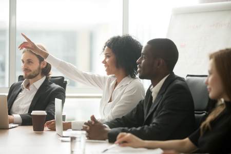 African woman raising hand to ask question at team training, curious black employee or conference seminar participant vote as volunteer at group office meeting with multiracial diverse businesspeople