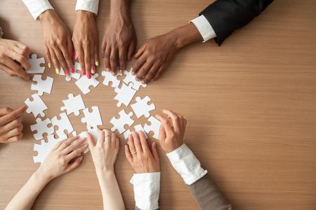 Hände des zusammenbauenden Puzzlespiels des multiethnischen Teams, gemischtrassige Gruppe Schwarzweiss-Leute, die Stücken am Schreibtisch, am erfolgreichen Teamwork-Konzept, an der Hilfe und an der Unterstützung im Geschäft, Abschluss herauf Draufsicht sich anschließen Standard-Bild