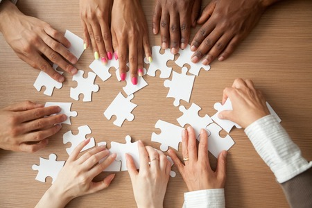 Ręce różnych ludzi układających puzzle, zespół afrykański i kaukaski układają elementy, szukając odpowiedniego dopasowania, pomagają w pracy zespołowej w znalezieniu wspólnej koncepcji rozwiązania, widok z góry