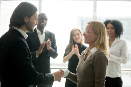 Boss handshaking employee congratulating with promotion while diverse colleagues clapping applauding, company ceo awarding appreciating motivating office worker for good work result by shaking hands Stock Photo