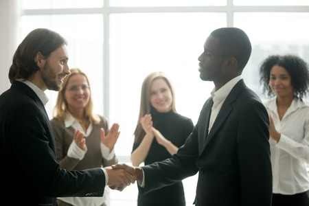 Smiling boss awarding congratulating african american employee with promotion shaking hands, ceo and team appreciating black manager for good work result by handshake applause, recognition concept