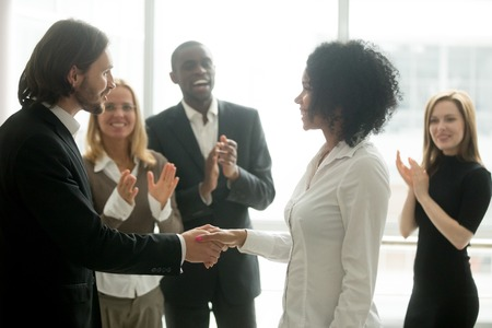 Grateful boss handshaking promoting african businesswoman congratulating with career achievement while colleagues applauding cheering successful worker, appreciation handshake, employee recognition Stockfoto