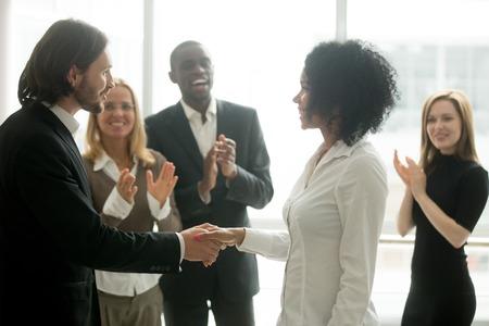 Dankbares Chefhändeschütteln, welches die afrikanische Geschäftsfrau beglückwünscht mit Karriereleistung während die Kollegen applaudieren, die erfolgreiche Arbeitskraft, Anerkennungshändedruck, Angestelltanerkennung zujubeln