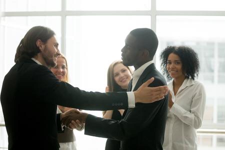 Patron de l'entreprise faisant la promotion d'un employé africain avec une poignée de main montrant de la gratitude, un partenariat ou une appréciation tandis que l'équipe commerciale applaudit pour féliciter un collègue avec un bon résultat
