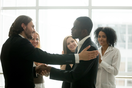 Company boss promoting african male employee with handshake showing gratitude, partnership or appreciation while business team clapping hands congratulating colleague with good result win recognition