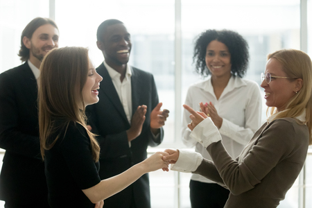 Funny smiling businesswomen holding hands celebrating success while diverse team applauding, female executive handshaking congratulating employee with common goal achievement, women power in business Stock Photo