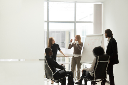 Diverse business team listening to female speaker discussing presentation on flip chart at meeting in boardroom, group brainstorm and marketing sales coaching corporate training concept, copy space