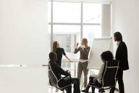 Equipo de diversos negocios escuchando a una oradora discutiendo la presentación en el rotafolio en la reunión en la sala de juntas, lluvia de ideas grupales y marketing de ventas, entrenamiento, concepto de capacitación corporativa, espacio de copia Foto de archivo