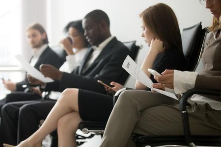 面接の準備のために列に並んでいる多民族の応募者、スマートフォン、人事、雇用、就職のコンセプトを使用して履歴書を保持する椅子で待ってい 写真素材