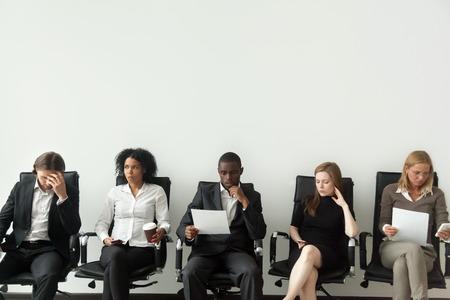 就職面接のコンセプトでのライバル、結果を待つライバルを見て並んで座っている好奇心旺盛な多民族の人々が、他の成功に嫉妬しながら、部屋を