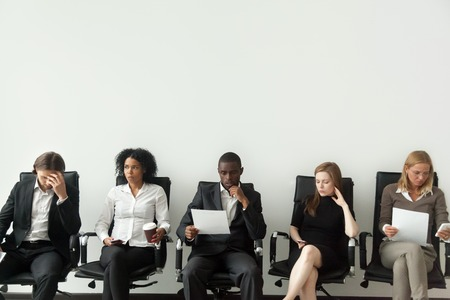 Rivalry at job interview concept, applicant walking in room while envious curious multiracial people sitting in row looking at rival waiting for result, winner and loser, jealous of other success