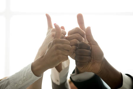 Multiracial team hands showing thumbs up finger gesture, motivated diverse corporate group showing like celebrating racial equality, successful teamwork, recommending business solution, close up view Stock Photo