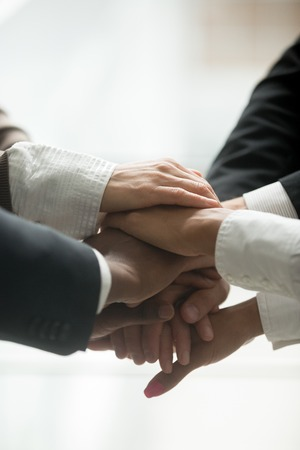 Stacked pile of hands close up vertical view, motivated multi-ethnic business team join together as concept of engagement and unity promising support in collaboration, help and commitment in teamwork Stockfoto - 97124138