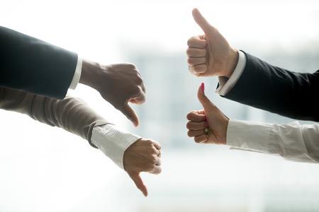 Hände von den verschiedenen Geschäftsleuten, die auf und ab Daumen zeigen, mögen gegen Abneigungsgeste, positives negatives Rückgespräch, ja und keine Oppositionsabstimmung, Konfrontationsunterschiede am Verhandlungskonzept