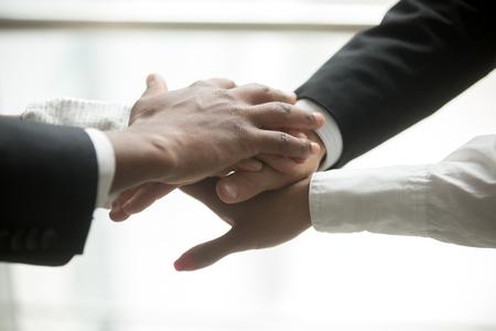 Afrikanische und kaukasische Partner schließen sich Händen im Stapel zusammen an, das motivierte gemischtrassige Geschäftsteam, das Hilfe und Unterstützung, Verpflichtung oder Einheit in der Zusammenarbeit, Verpflichtung in der Teamarbeit, nahe hohe Ansicht verspricht Standard-Bild