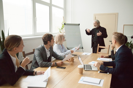 Experienced business coach giving presentation to executive managers team explaining strategy with flip chart, senior company leader presenting employees new corporate plan at conference room meeting Foto de archivo
