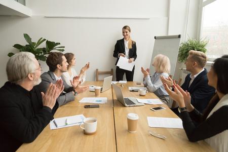 Ältere und junge Wirtschaftler, die Geschäftsfrau nach Darstellung bei der Konferenzsitzung applaudieren, klatschende Hände der dankbaren Gruppe, die lächelndem Teamleiter-, Anerkennungs- oder Glückwunschkonzept zujubeln Standard-Bild