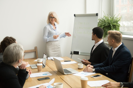 Senior woman boss leading corporate team meeting presenting team goals, smiling aged businesswoman company leader or business teacher giving presentation coaching diverse employees group in boardroom 版權商用圖片
