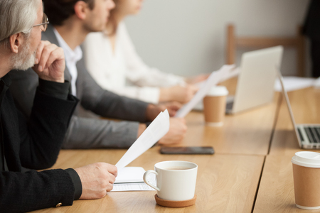 Attentive senior businessman holding documents focused on listening at group meeting, aged experienced investor, client or company executive participating training conference business seminar concept Banco de Imagens