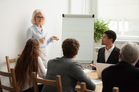 Aged attractive businesswoman giving presentation at corporate diverse group meeting, senior female business coach, woman boss or team leader presenting new strategic plan to multiracial employees Foto de archivo