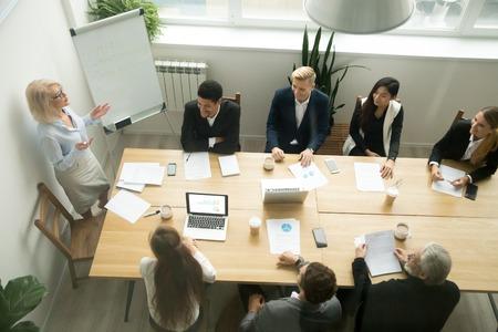 Gealterte ältere Geschäftsfrau, die Darstellung bei der gemischtrassigen Gruppenbürositzung, beim weiblichen Teamleiter, beim Firmenchef oder beim Geschäftstrainer darstellt Unternehmensplan den Führungskräften im Sitzungssaal, Draufsicht gibt Standard-Bild