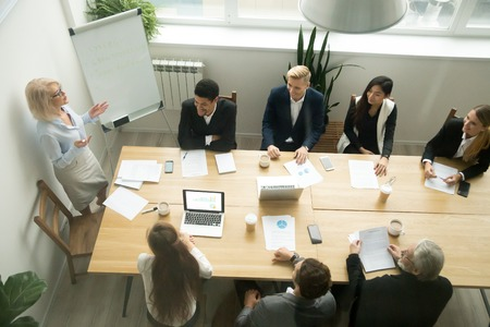 Aged senior businesswoman giving presentation at multiracial group office meeting, female team leader, company boss or business coach presenting corporate plan to executives in boardroom, top view Stockfoto
