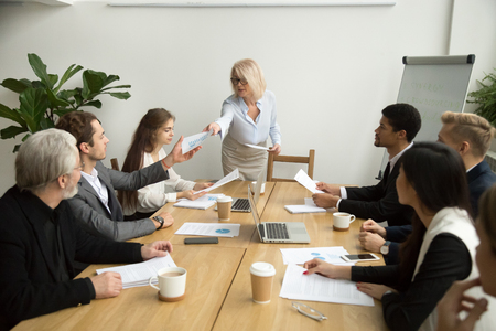 Senior businesswoman company boss ceo handing financial statistical report to executive manager giving instructions discussing work results at corporate diverse team group meeting in boardroom