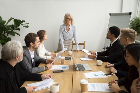 Serious aged businesswoman leading corporate team meeting talking to multiracial employees, senior female boss ceo leader discussing work with diverse subordinates at company group briefing