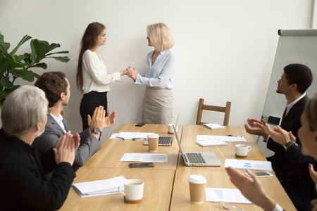 Senior businesswoman boss promoting female employee thanking for good work holding hands as trust and support concept while team applauding congratulating colleague at group meeting, recognition