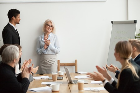Smiling senior businesswoman boss and team clapping hands at meeting, happy woman executive applauding celebrating business success or congratulating african manager with promotion at group meeting 版權商用圖片