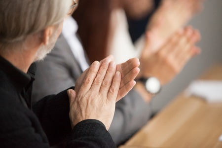 Senior gray-haired businessman clapping hands attending conference, aged training participant applauding at group meeting, old man expressing appreciation or congratulation, rear view, focus on hands Stockfoto - 97384811