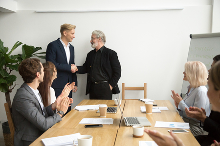 Senior gray-haired businessman boss promoting male employee thanking appreciating good work shaking hands while team applauding congratulating at group meeting, trust, recognition, support concept Stock Photo