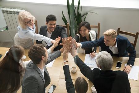 統一コンセプトを示す高い5つの意欲的な多民族ビジネスチーム、若いと古い企業グループが協力して有望なサポートを手に入れ、チームワークでの