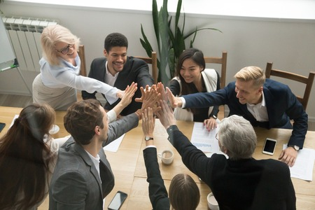 Diverso gruppo multietnico motivato di affari che dà il concetto di unità di cinque che mostra l'unità, gruppo aziendale giovane e vecchio unire le mani promettente supporto in collaborazione, aiutare l'impegno nel lavoro di squadra, vista dall'alto