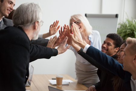 Multiracial young and senior business people join hands giving high five together, motivated diverse team showing team spirit synergy in goal achievement, promising help, supporting unity in teamwork Stock fotó