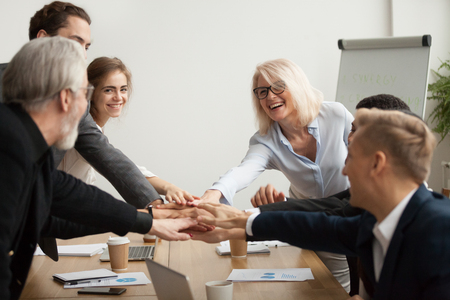Happy smiling corporate team of senior executives and young employees join hands together at group meeting, business people celebrating success achievement unity, promising help support in teamwork Stock Photo