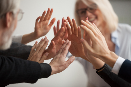 Hands of diverse business people giving high five, smiling team members, teachers and students promising help unity in goal achievement, coaching support in mentoring teamwork concept, close up view Archivio Fotografico
