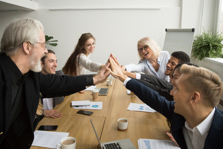 Diverse young and senior business people giving high five building successful team at meeting, motivated multiracial group of different age uniting celebrating win promising support help in teamwork Foto de archivo