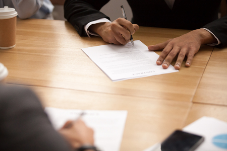 Businessman in suit signing business contract at meeting, entrepreneur putting written signature filling legal document at negotiations, two partners making partnership deal concept, close up view