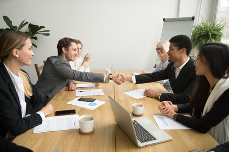 Diverse businessmen shaking hands after signing contracts at group multiracial meeting, african and caucasian partners in suits handshaking promising good deal after successful negotiations concept Stock Photo