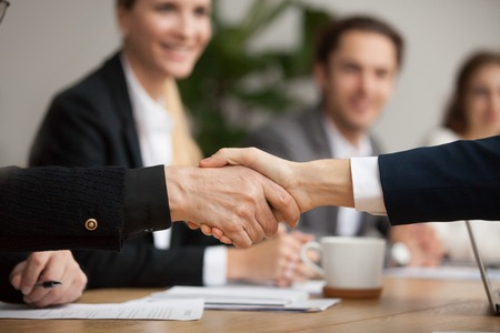 Hands of senior and young businessmen shaking at group meeting, two partners of different age handshaking making agreement or good deal, concluding contract help support concept, close up view