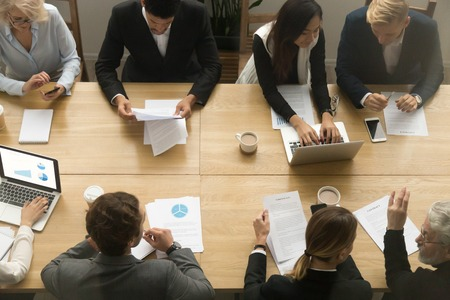 Diverse senior and young business people sitting at conference table working together using devices and talking at group office meeting, corporate project team coworking teamwork concept, top view