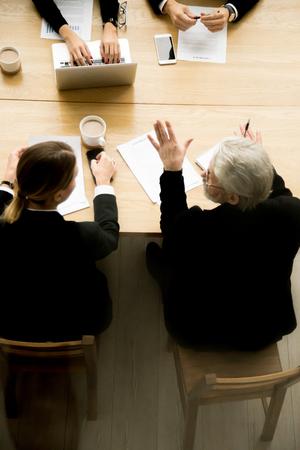 Älterer Geschäftsmann, der bei den Gruppenverhandlungen unter Vertrag spricht, erfahrener gealterter Investor, der weiblichen Partner bei der Teamsitzungsplanungsgeschäfts-Abkommenvereinbarung, vertikale Draufsicht beratend verhandelt