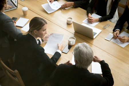 Negotiations concept, different businesspeople discussing deal details at group meeting, young and senior partners team thinking talking consulting about contract sitting at conference office table Foto de archivo