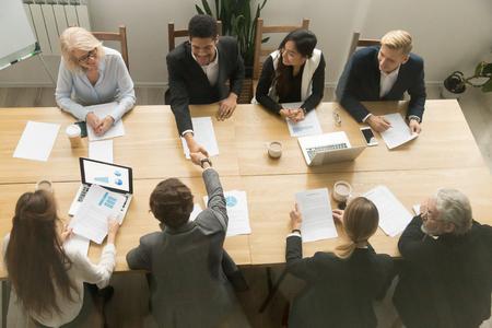 Gelukkige multiraciale zakenlieden schudden elkaar de hand op diverse groepsbijeenkomsten, zwart-wit partners handenschudden na succesvol teamwerk of teamonderhandelingen zittend aan vergadertafel, bovenaanzicht overhead Stockfoto