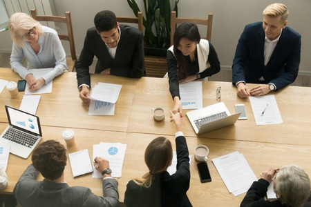 Smiling asian and caucasian businesswomen shaking hands over conference table at diverse team group meeting, multi-ethnic female partners handshaking after successful negotiations teamwork, top view