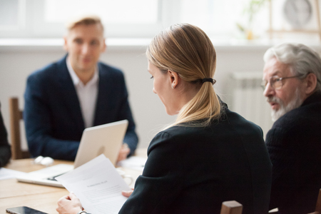 Serious businesswoman reading document contract at team meeting, female employee or manager holding paper at negotiations, focused company executive analyzing report during corporate group briefing