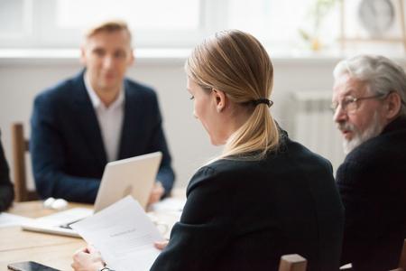 Poważna bizneswoman czyta umowę dokumentu na spotkaniu zespołu, pracownica lub kierownik trzymający papier podczas negocjacji, skoncentrowany dyrektor firmy analizujący raport podczas odprawy grupy korporacyjnej Zdjęcie Seryjne